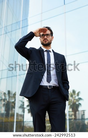 Cropped portrait of confident and serious businessman looking into the distance holding up his hand standing in the city - stock photo