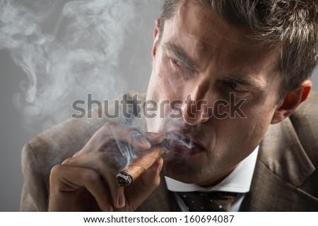 Cropped portrait of hard gaze businessman while smoking a cuban cigar - stock photo