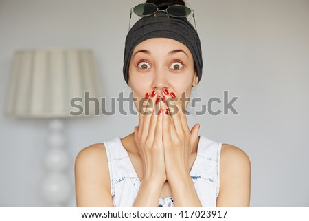 Cropped portrait of shocked girl covering her mouth looking at the camera with stunned and surprised face expression while listening to some unbelievable story during conversation with her friend  - stock photo