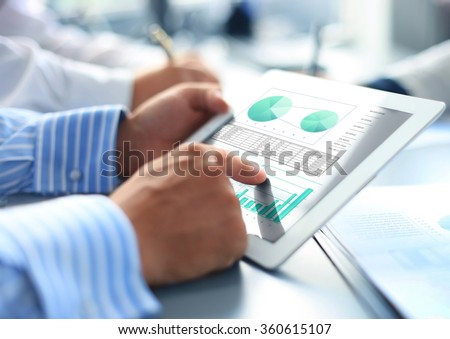 Cropped shot of a group of businesspeople looking at graphs on digital tablets - stock photo