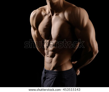 Cropped shot of a male bodybuilder showing off his ripped abs posing shirtless in studio - stock photo