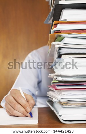 Cropped shot of a man writing document behind a stack of folders at desk - stock photo