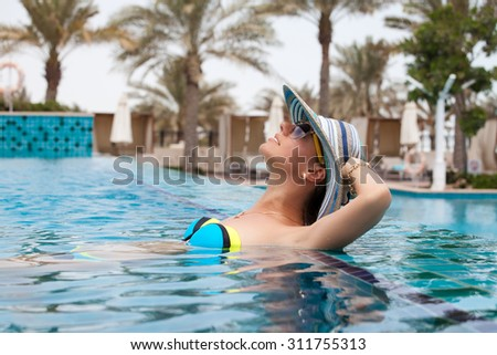 Cropped shot of a sexy cheerful woman relaxing in a luxury swimming pool. Girl at travel spa resort pool. Summer luxury vacation. - stock photo