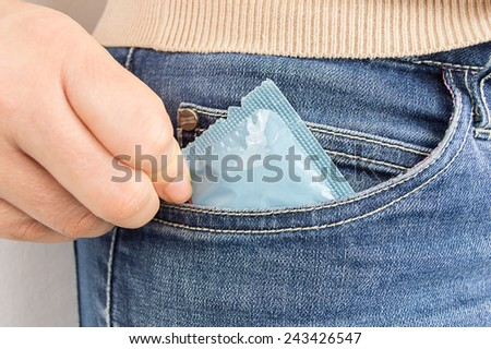 cropped  shot of a woman s pocket taking the condom - stock photo