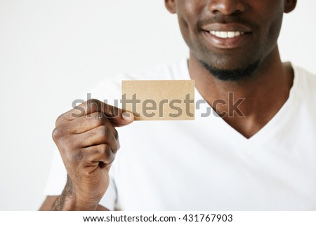 Cropped shot of African male hands holding blank card with copy space for your text or advertising content. Successful smiling businessman wearing white T-shirt showing business card. Film effect - stock photo