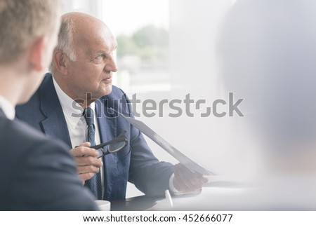 Cropped shot of an elegant senior boss at the meeting with his business partners - stock photo