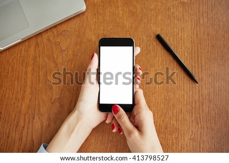 Cropped shot of female manager chatting on cell phone during short break while working in the office. Close up view of woman's hands typing message, checking e-mail on mobile phone with blank screen - stock photo