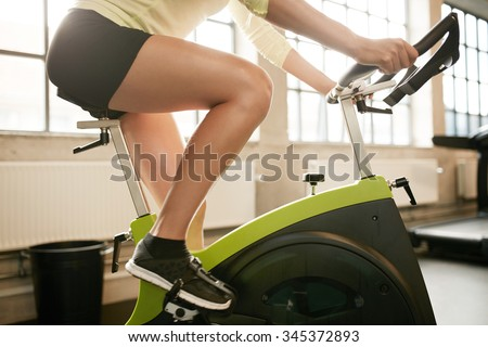 Cropped shot of fitness woman working out on exercise bike at the gym. Female exercising on bicycle in health club, focus on legs. - stock photo