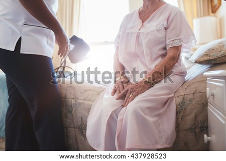 Cropped shot of home caregiver with senior woman sitting on bed. Female doctor visiting her senior patient at home. - stock photo