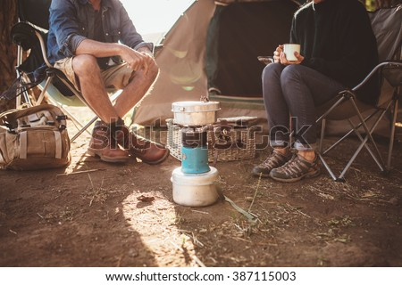 Cropped shot of mature couple sitting around a camp stove. Man and woman sitting in chair outside tent at their campsite. - stock photo