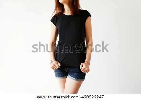 Cropped shot of young Caucasian brunette model in blank black T-shirt and jeans shorts. Female office worker wearing casual clothes at home after hard working day in the office. Lifestyle concept - stock photo