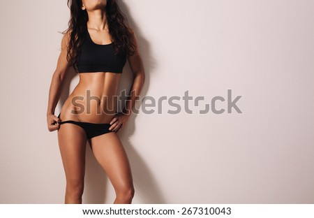 Cropped shot of young woman in sporty lingerie posing against a wall. Sexy young woman with muscular body. Slim and fit female model. - stock photo