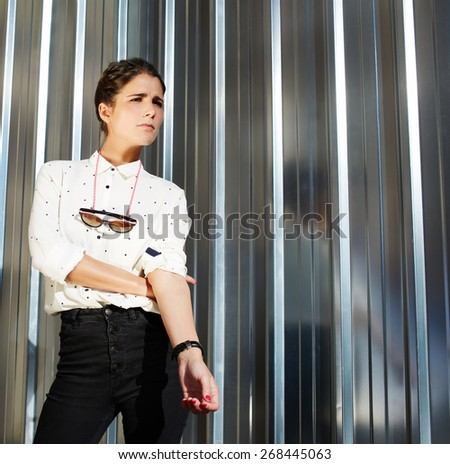 Cropped shot portrait of attractive brunette hipster woman posing on shiny wall background, fashionable model standing on silver background looking away - stock photo