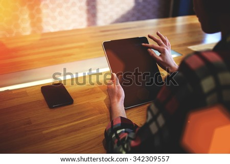 Cropped shot view of a young woman student touching digital tablet screen while sitting in modern coffee shop, female holding touch pad with copy space screen for your text message or advertising  - stock photo