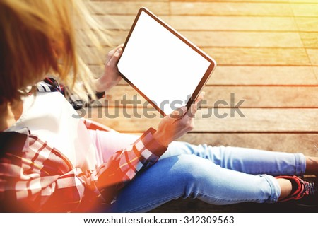 Cropped shot view of blonde woman holding touch pad with blank copy space screen for your text message or advertising content,young female hipster student use digital tablet while resting on a campus  - stock photo