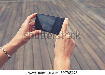 Cropped shot view of female tourist taking picture with her smart phone in urban setting, woman's hands holding cell telephone with copy space area for your text message or advertising content - stock photo