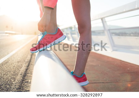 Cropped shot view of young fit woman tie shoelaces while standing on a road during jogging in summer evening, sporty girl tying the laces on running shoes while taking break between training outside  - stock photo