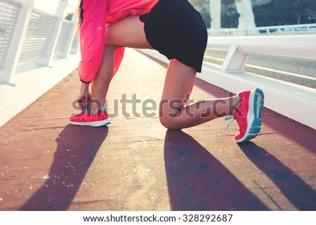 Cropped shot view of young sporty girl tie shoelaces while standing on a road in summer evening, athletic woman tying the laces on running shoes while taking break between intense jog in the fresh air - stock photo