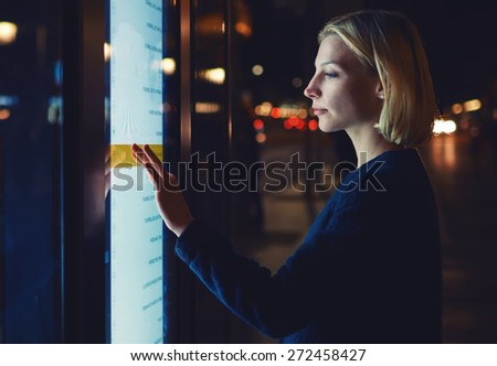 Cropped shot young woman touching sensitive screen of smart bus stop in Barcelona, female using touristic information self service with modern digital device while standing at night with city lights - stock photo