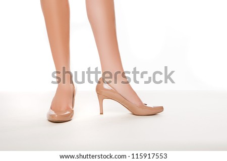 Cropped view image of the shapely legs of a woman in stylish simple high heeled shoes on a white background - stock photo