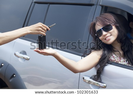 Cropped view of a hand giving a car key to beautiful asian woman - stock photo