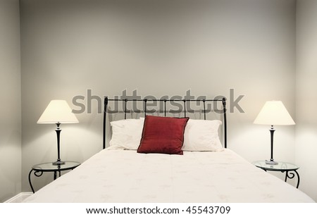 Cropped view of a white bedroom, showing a bed and two lamps on side tables. Horizontal format. - stock photo
