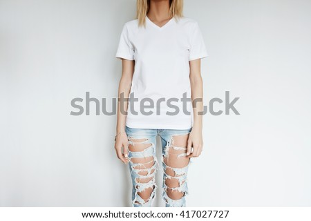 Cropped view of blonde slim girl wearing blank T-shirt with copy space for your content. Young woman in ripped jeans posing isolated against blank white wall. Advertising and T-shirt design concept  - stock photo