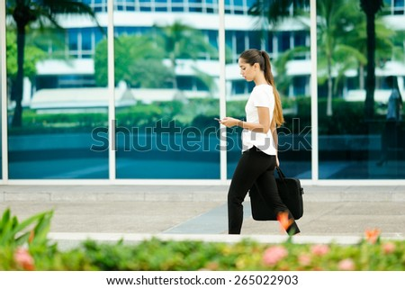Cropped view of business woman walking in city street with laptop bag, chatting on mobile phone and going to work in the morning - stock photo
