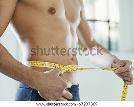 cropped view of caucasian young man measuring waist with yellow tape. Horizontal shape, mid section, side view - stock photo
