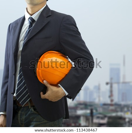 Cropped view of engineer holding helmet  - stock photo