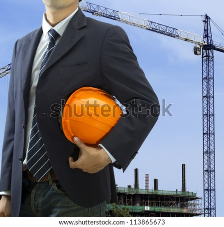 Cropped view of engineer holding helmet standing in front the city - stock photo