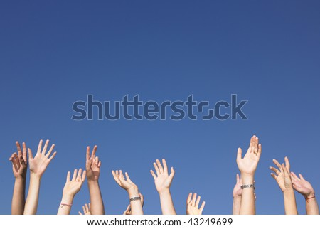 Cropped view of group of people with arms raised against a blue sky. Horizontally framed shot. - stock photo