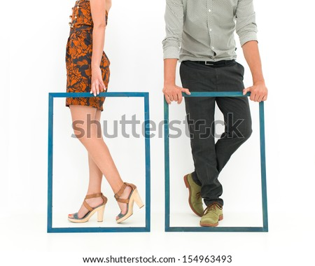 cropped view of man and woman legs behind two empty frames, on white background - stock photo