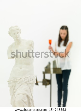 cropped view of replica of Venus de Milo statue with a woman looking at an artwork in blurred background - stock photo