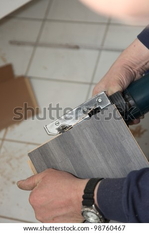 Cropped view of the hands of a handyman trimming tiles with a cutter above a tiled floor in a DIY concept - stock photo