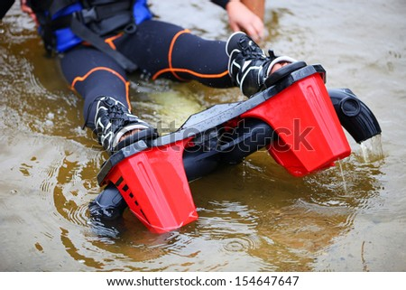 Cropped view of woman wearing flyboard boots and sitting in shallow water before a ride - stock photo