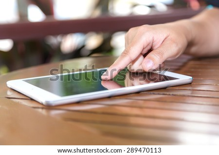 Cropped view of women using a digital tablet at outdoor coffee shop - stock photo