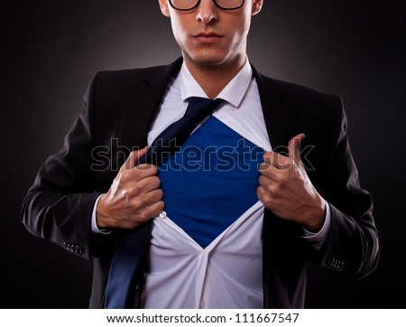 Cropped view of young business man tearing off his shirt on black background - stock photo