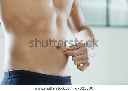 cropped view of young caucasian man measuring fat on belly. Horizontal shape, mid section, side view, copy space - stock photo