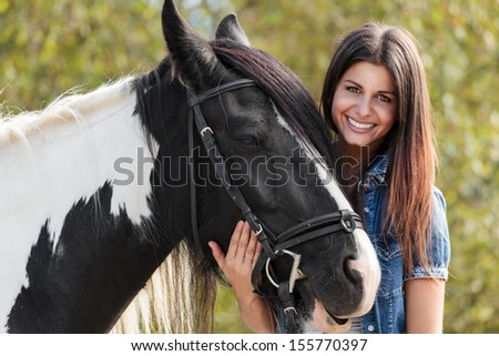 cropped view of young female rider smiling and embracing her horse - stock photo