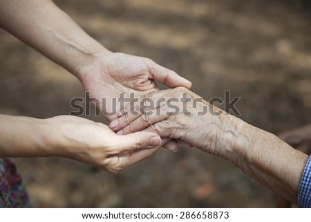 Cropped view of young woman holding hand of senior person - stock photo