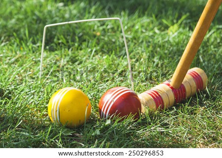Croquet Mallet and Hoop with Red and Yellow Balls - stock photo