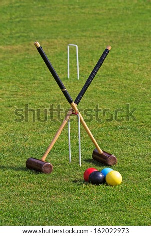 Croquet mallets, balls and hoops ready for a game - stock photo