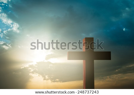 cross against sun rays shining through clouds - stock photo