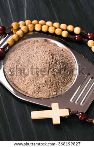 Cross and ash - symbols of Ash Wednesday. Shallow depth of field. - stock photo
