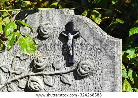 Cross and flower on the tombstone in the public cemetery - stock photo
