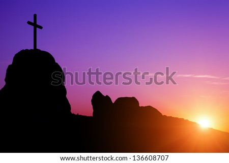 Cross and Sunrise, Sunset - Single cross on a rocky hilltop. - stock photo