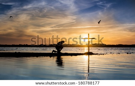 Cross at a lake with a man in prayer beside it, as the sun goes down. - stock photo