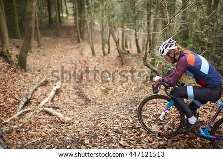 Cross-country cyclist resting on bike with water bottle - stock photo