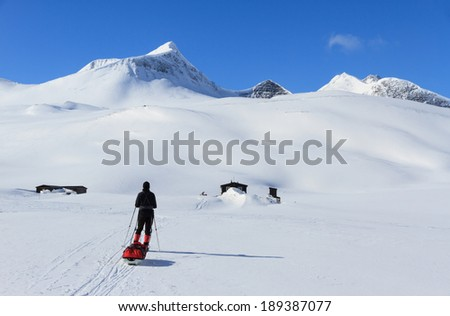 Cross country skier with pulka (sled) near the Nallo mountain hut in Lapland, Sweden. - stock photo